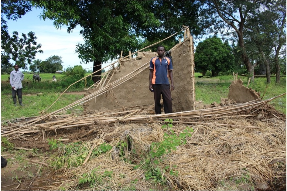 Picture of Figure 2: Boniface Kayange standing by his fallen house due to the flooding waters that passed through his house
