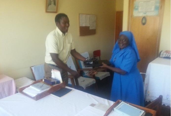 Picture of Mr Vincent Shaba, Health Desk Officer, hands over a laptop computer