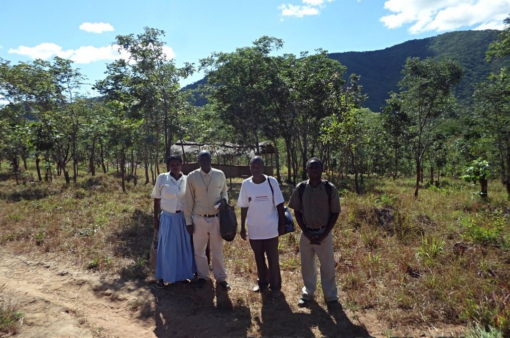 Led by Mr Mhango of Juma (far right) the four stand at the site where the Juma Catholic Community conngreagate for liturgy in the shelter behind them