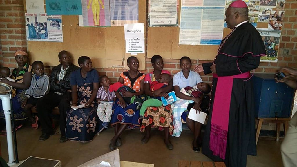 Bishop Mtumbuka interacting with beneficiaries of health services offered by Kaseye Community Hospital