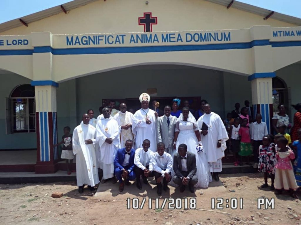 Bishop Mtumbuka flanked by the Vicar General, the Nyondo Family and other priests after the opening Mass