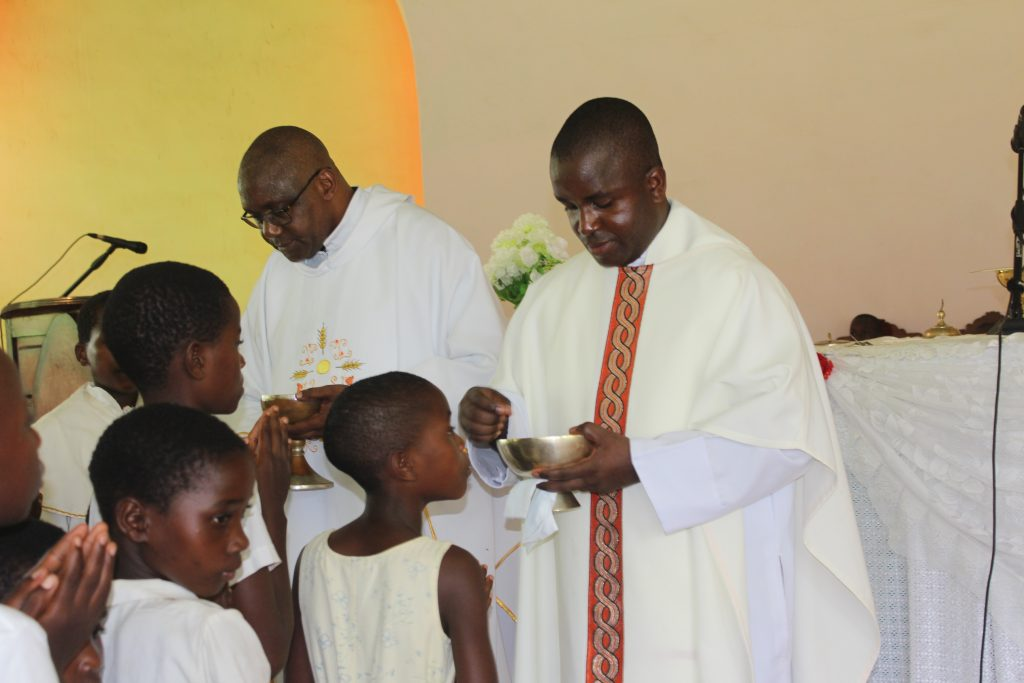 The Vicar General (in specs) and Father Simwela distributing communion during the event