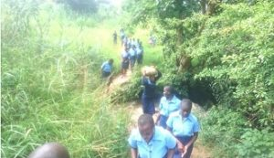 g9 Girls crossing a stream on their way to the surrounding villages