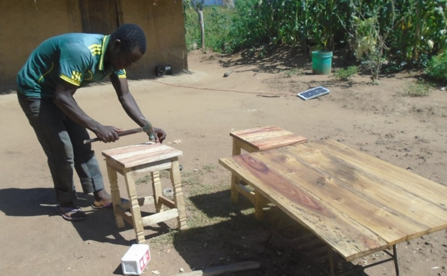 Jimu Msukwa at his carpentry shop early this year making final touches on his products