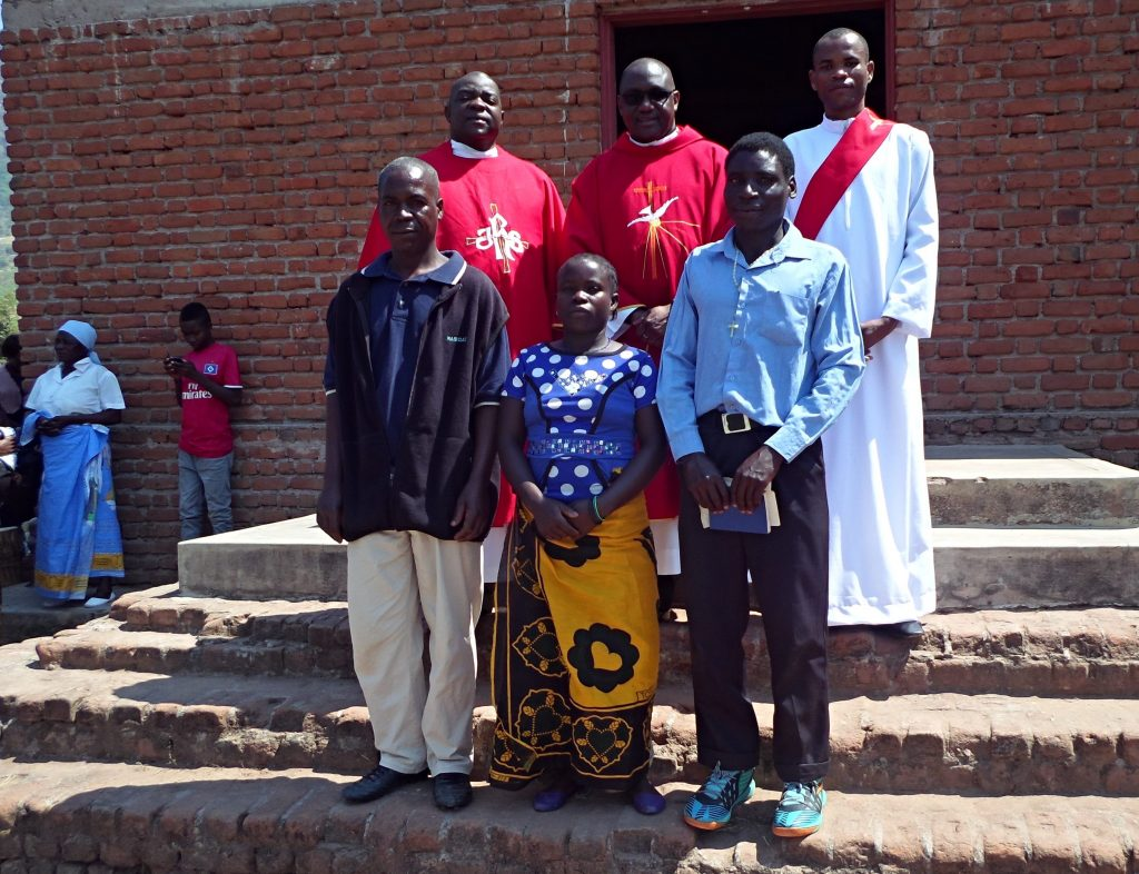 Innocent Harawa (with hymn book in his hands), Nancy Kapira (lady) and Kumbukani Nyirenda (next to Nancy) have a photo with the Vicar General (in specs behind Nancy).