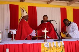 Bishop Mtumbuka Hands Over a Certificate to One of the Newly Ordained Priests